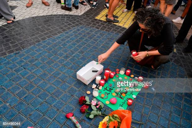 A woman lights a candle next to first flowers and a message to the victims on August 18 2017 on the spot where yesterday a van ploughed into the...