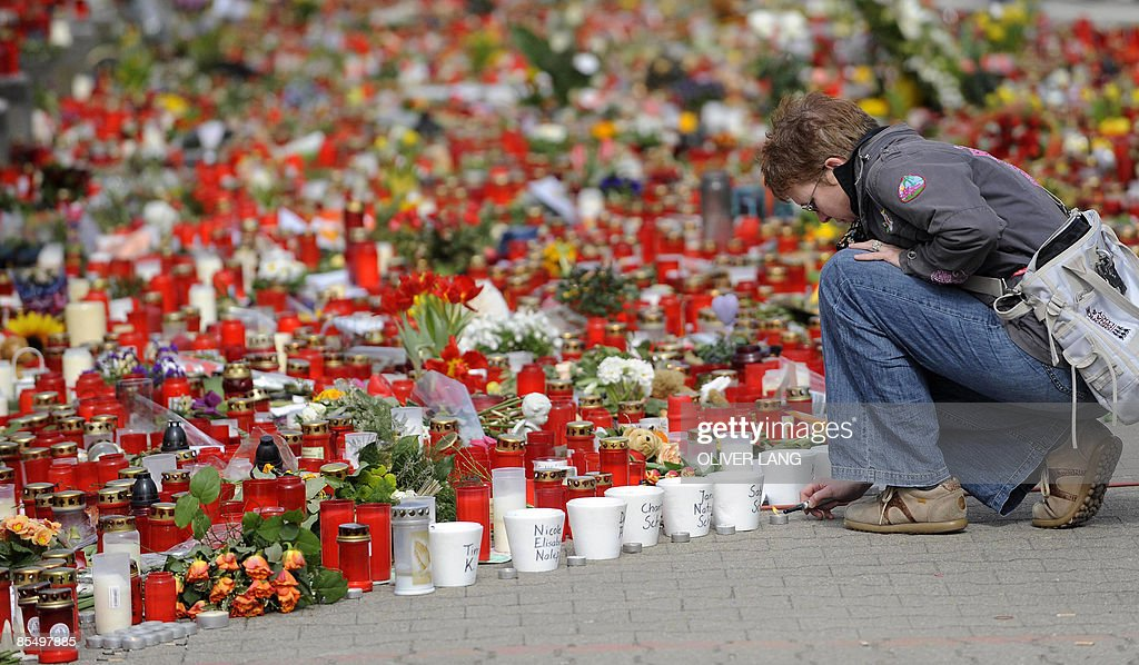 A woman lights a candle on March 19 2009 in front of the Albertville secondary school in Winnenden southern Germany where a teenager went on the...