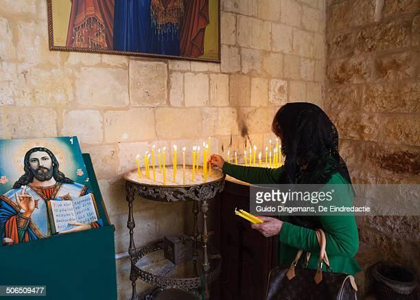 Woman lights candle at St George church (Jordan)