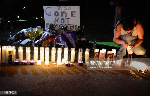 A woman lights candles at a makeshift memorial for victims of the Century 16 movie theatre where a gunmen attacked movie goers during an early...