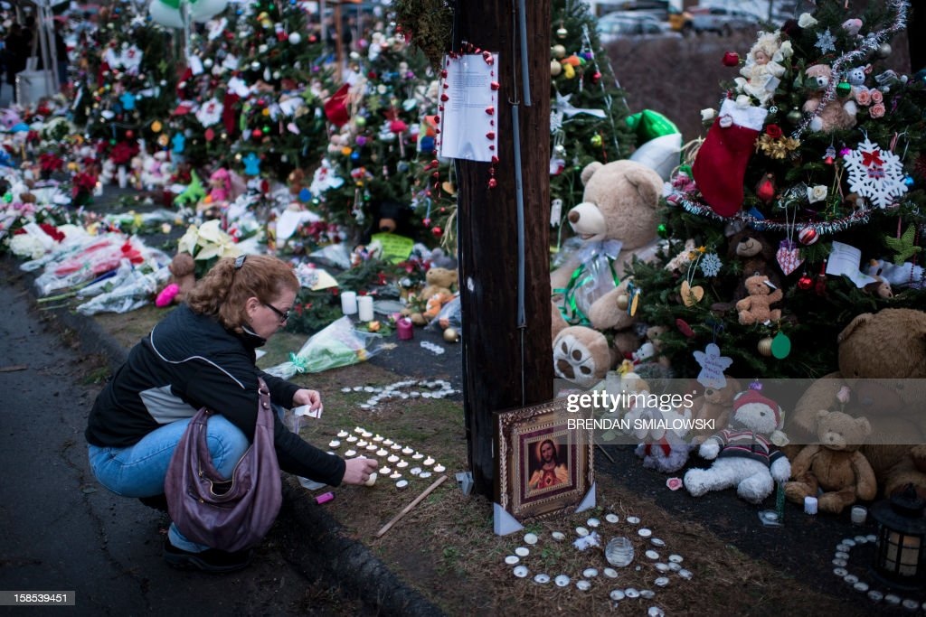 A woman lights candles at a makeshift memorial near the entrance to the grounds of Sandy Hook Elementary School on December 18, 2012 in Newtown, Connecticut. Students in Newtown, excluding Sandy Hook Elementary School, return to school for the first time since last Friday's shooting at Sandy Hook which took the live of 20 students and 6 adults. AFP PHOTO/Brendan SMIALOWSKI