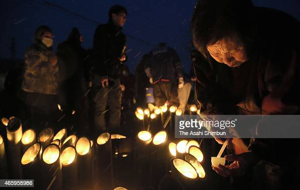 A woman lights candles at a temporary housing in commemoration for the vicitms at a temporary housing on the fourth anniversary of the Great East...