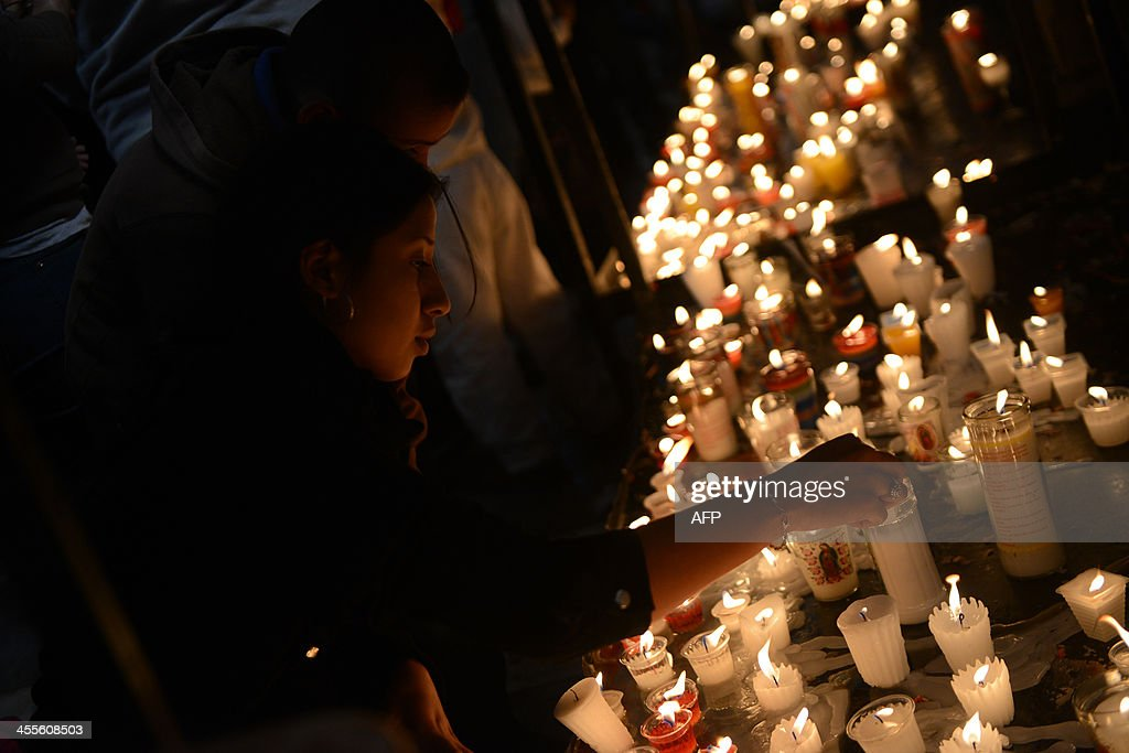 A woman lights candles on December 12 at the Basilica of the Virgin of Guadalupe in downtown Guatemala City during the celebration of the appearance...
