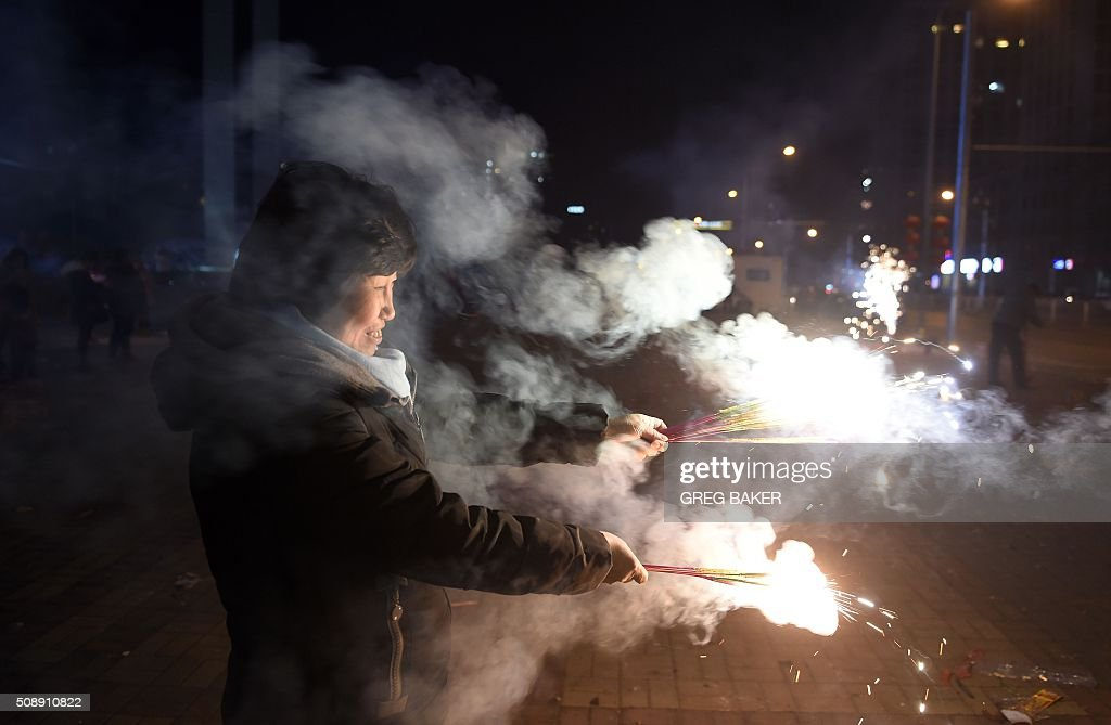 A woman lights fireworks on a street in Beijing on February 7, 2016, the eve of the Lunar New Year. China marks the beginning of the Lunar New Year, the Year of the Monkey, on February 8. AFP PHOTO / GREG BAKER / AFP / GREG BAKER