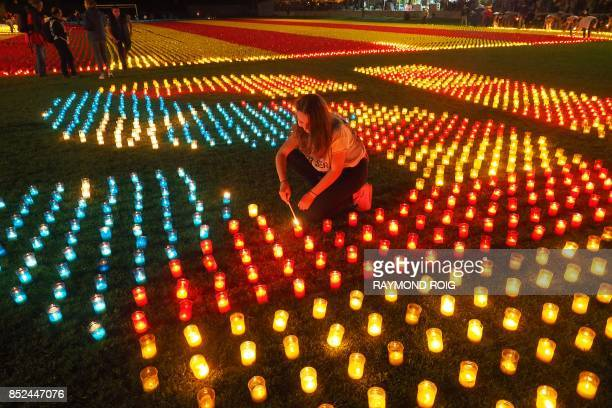 A woman lights one of the 82000 candles making a Catalonian independence flag in Llivia in the Spanish Pyrenees near the French and Andorran borders...