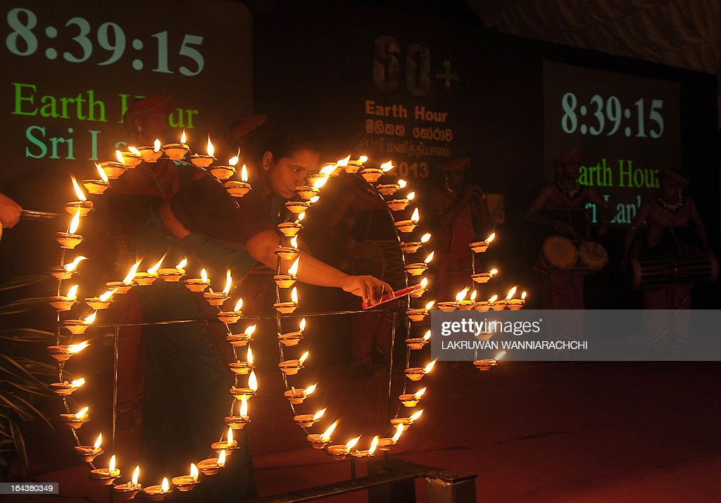 A woman lights up oil lamp to mark Earth Hour, on March 23, 2013 in Colombo. Millions of people were expected to switch off their lights for Earth Hour on March 23, in a global effort to raise awareness about climate change. Since it began in Sydney in 2007, Earth Hour has grown to become what environmental group WWF says is the world's largest demonstration of support for action on carbon pollution.
