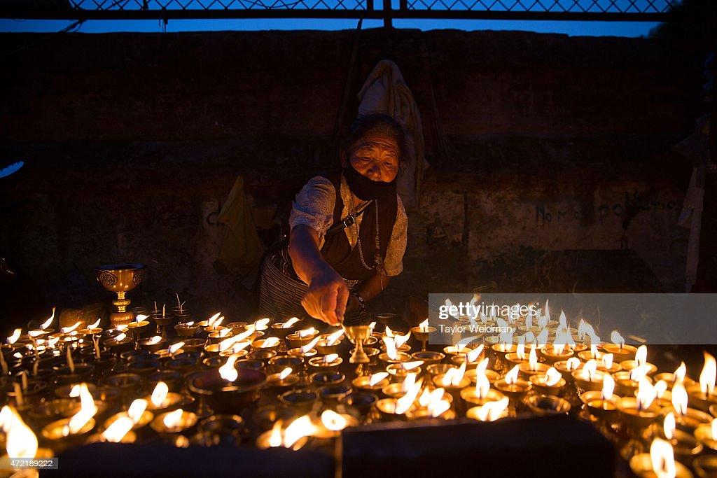 A woman lights votive candles as she celebrates the anniversary of Buddha's birth at Boudhanath Stupa in Kathmandu Nepal on May 4 2015 On April 25...