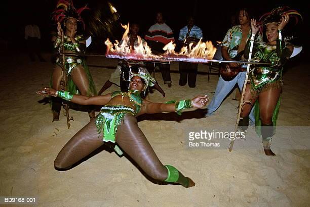 Woman limbo dancing on beach, night