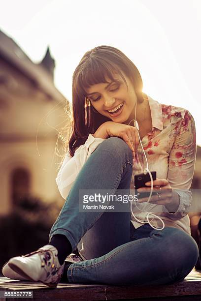 Woman listening music from phone in street