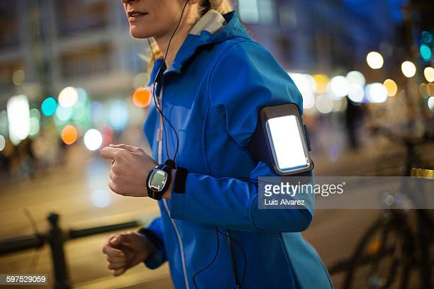Woman listening music while jogging in city