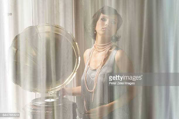 Woman listening to gramophone behind the curtain