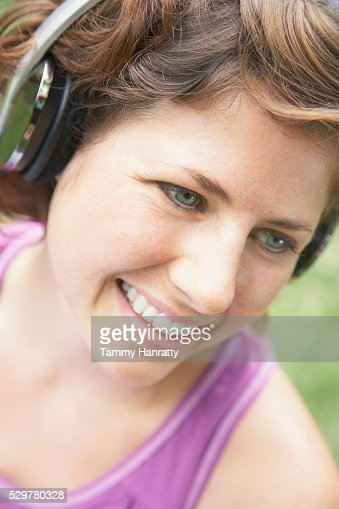Woman listening to headphones and smiling : ストックフォト