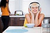 Woman listening to headphones at breakfast table