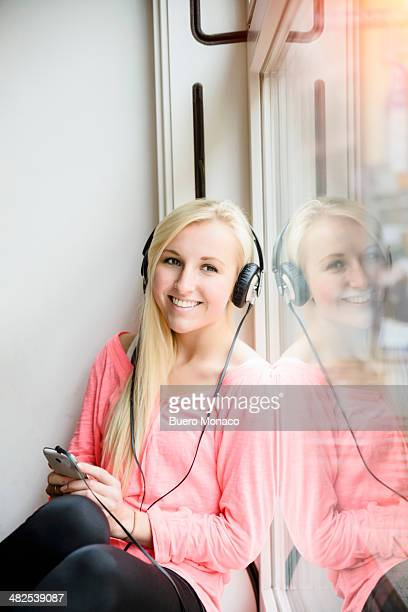 Woman listening to headphones in a cafe, smiling