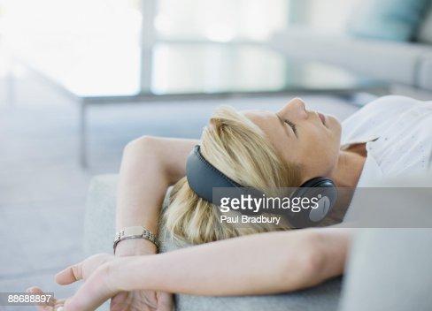Woman listening to headphones in living room : Bildbanksbilder