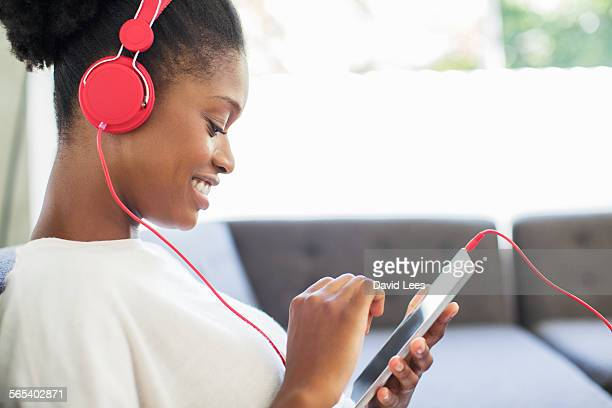 Woman listening to headphones on sofa