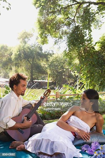 Woman listening to man play guitar