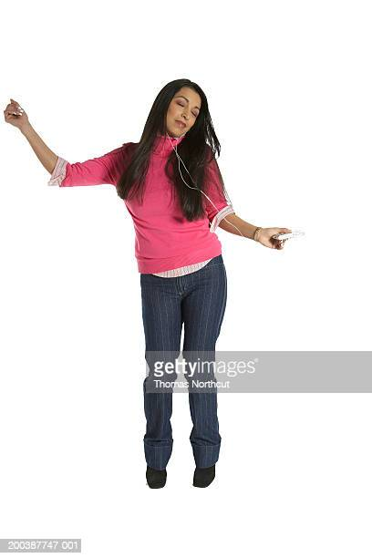 Woman listening to MP3 player and dancing, eyes closed