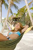 Woman listening to mp3 player in hammock on beach