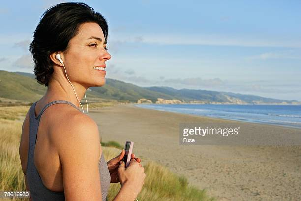 Woman Listening to MP3 Player on Beach