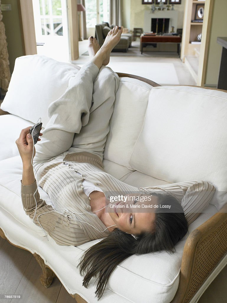 Woman listening to MP3 Player on sofa indoors smiling. : Stock Photo