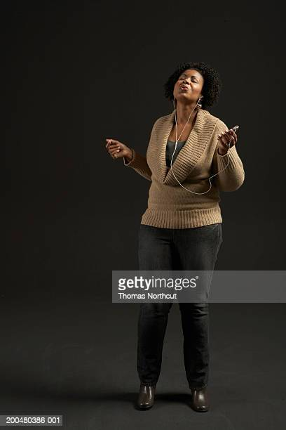 Woman listening to MP3 player, singing