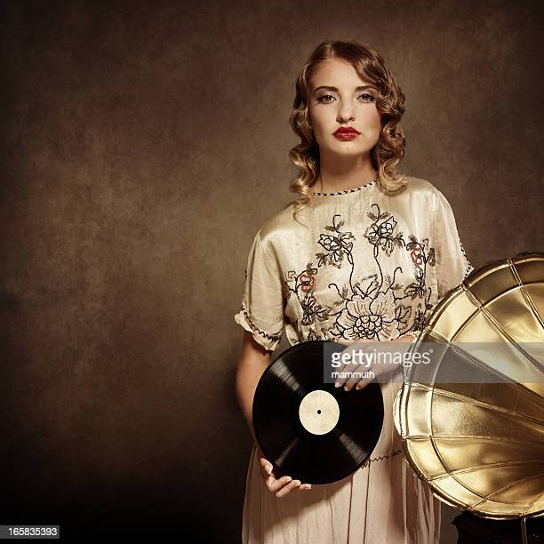 woman listening to music and holding an old vinil record