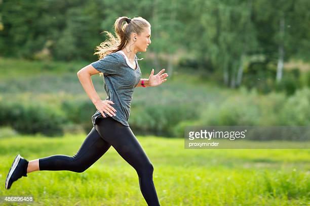 Frau Musik hören im park und Laufen