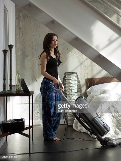 Woman listening to music and vacuuming bedroom