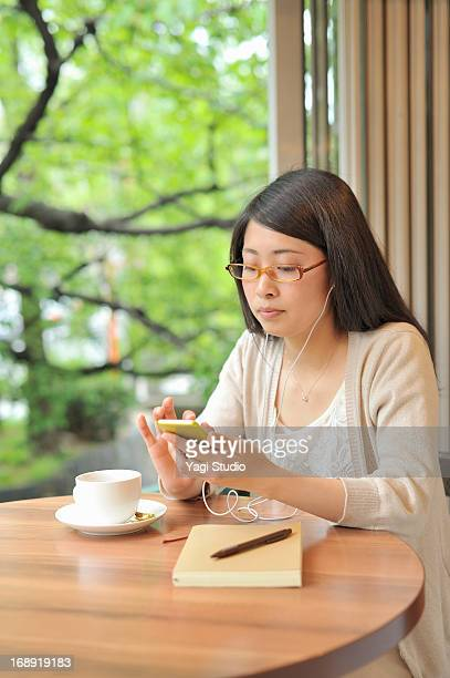 Woman listening to music in a cafe