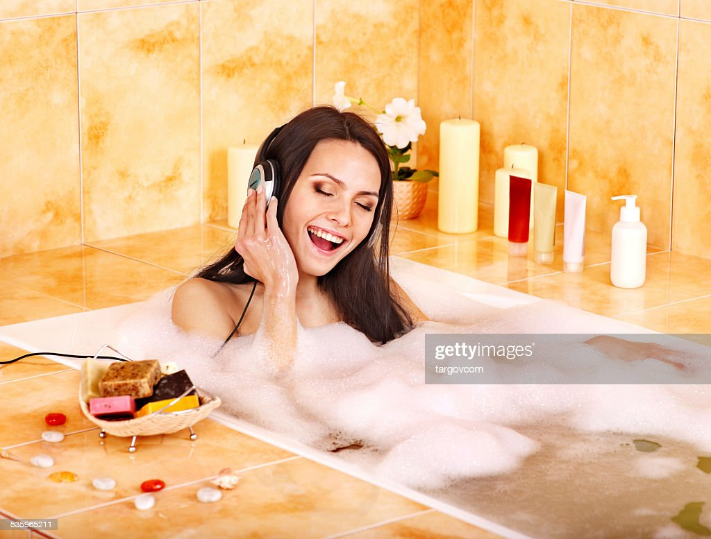 Woman listening to music in bath : Stock Photo