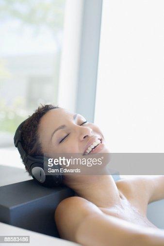 Woman listening to music in bathtub : Stock Photo