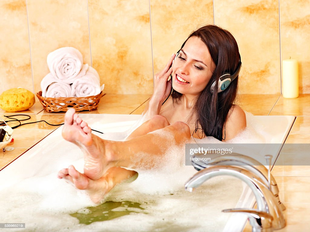 Woman listening to music in bubble  bath : Stock Photo
