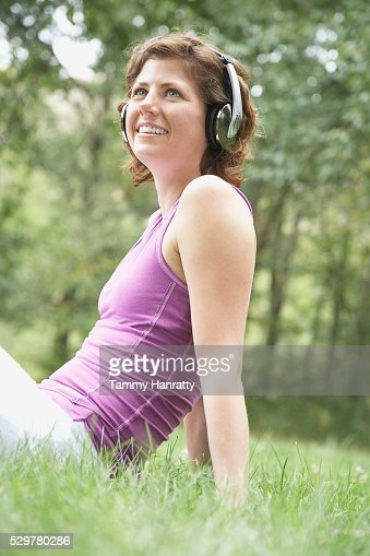 Woman listening to music in the park : Stock Photo