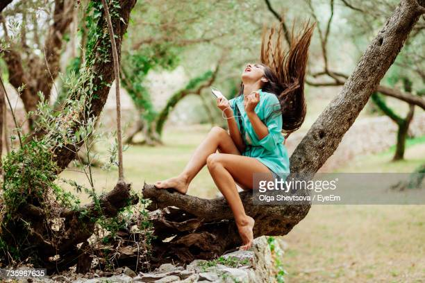 Woman Listening To Music In Tree
