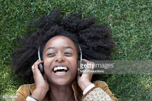 Woman listening to music lying on grass : Stock Photo