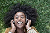 Mujer escucha música lying on grass