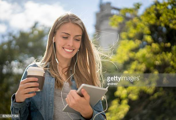 Woman listening to music on her tablet outdoors