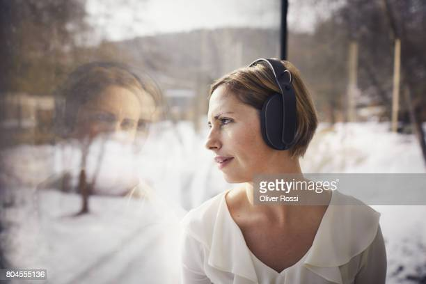 Woman listening to music with headphones looking out of the window