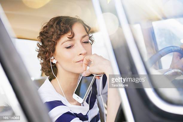 woman listening to music with mobile in car