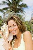Woman listening to seashell on beach