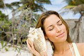 Woman listening to seashell on beach