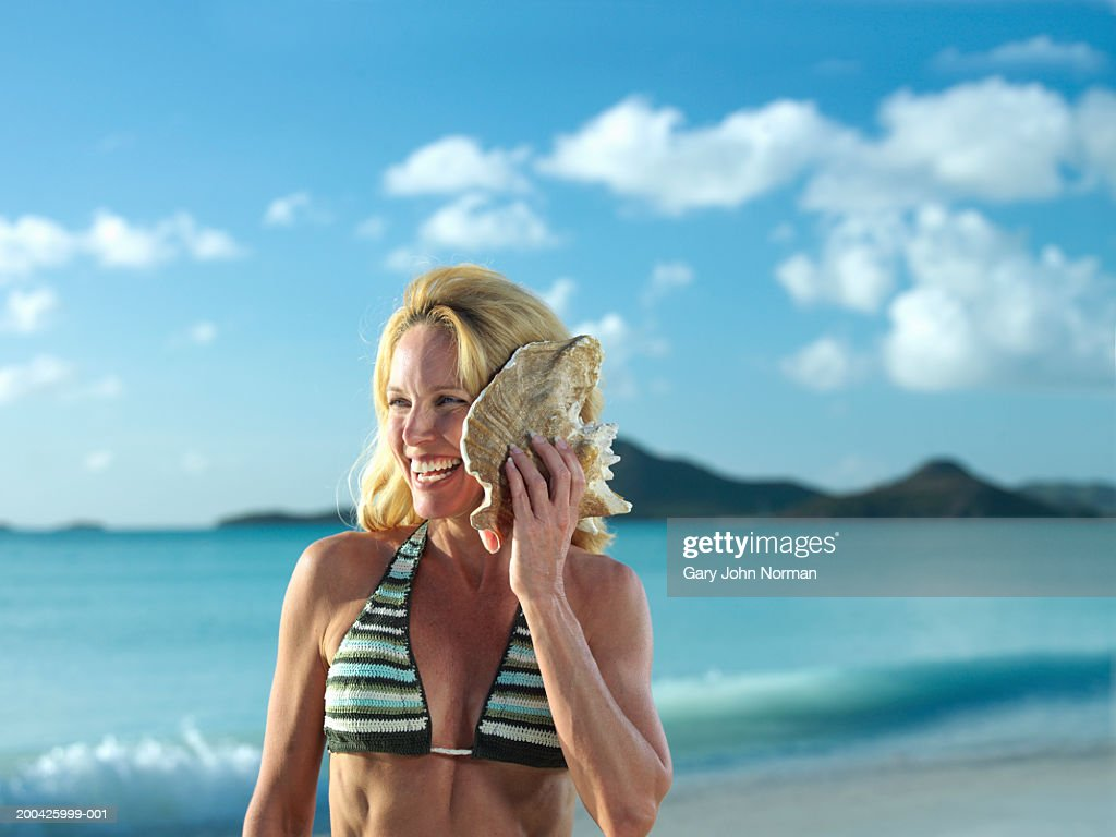 Woman listening to shell on beach, smiling, close-up