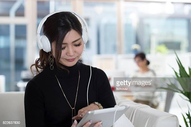 女性の音楽を聞きながら、タブレット