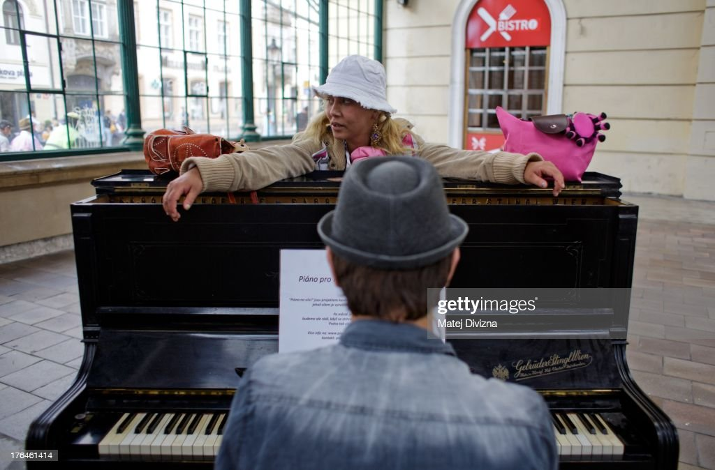 A woman listens as a man plays piano during the first day of the 'Pianos on the street' project at the Masaryk railway station on August 13, 2013 in Prague, Czech Republic. The project, by Prague cafe owner Ondrej Kobza, started in Prague today. Kobza placed pianos in five spots in the city centre for random passers-by to play. Similar projects run worldwide.