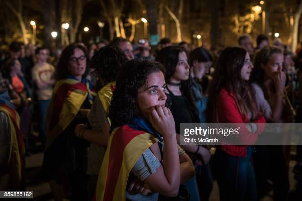 A woman listens on as she watches a big screen after Catalan President Carles Puigdemont suspended the declaration of independence outside the...