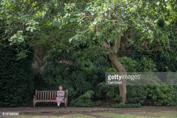 A woman listens to the Cobham Brass Band playing in College Garden in the grounds of Westminster Abbey on July 19 2017 in London England A series of...