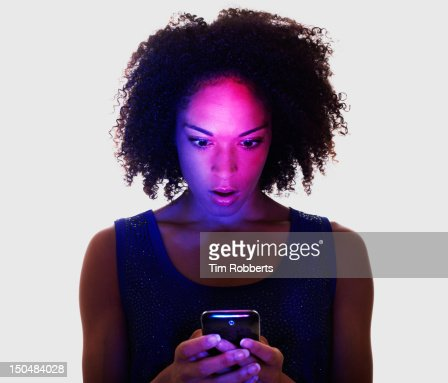 Woman lit by smart phone looking surprised. : Stock Photo