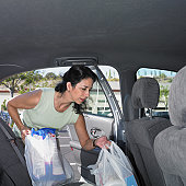 Woman loading bags of groceries into her car