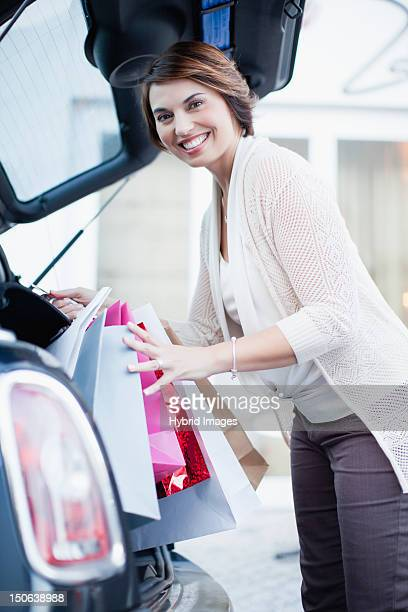 Woman loading shopping into trunk